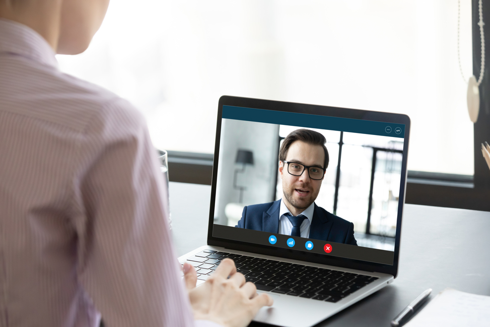 Female employee talking with male colleague or business partner using virtual video call on laptop